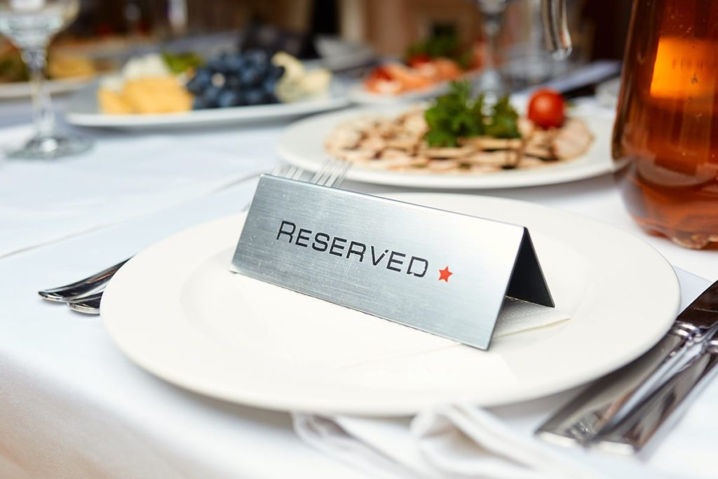 photo of a table at a restaurant with food and a reserved sign in front of the plate